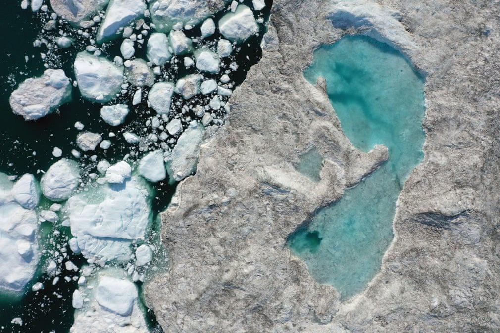 """Bề mặt một tảng băng trôi xuất hiện """"hồ nước"""" do nhiệt độ cao khiến băng tan chảy. Bức ảnh được chụp tại Greenland, khu vực chịu ảnh hưởng nặng nề vì biến đổi khí hậu. Mùa hè tại xứ sở băng giá này bắt đầu kéo dài hơn trong nhiều thập kỷ qua. Sông băng và các chỏm băng cũng dần biến mất. Ảnh: Sean Gallup/Getty Images."""