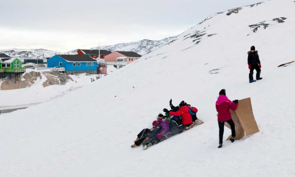 Trẻ em trượt tuyết trên các mảnh bìa cứng được tìm thấy ở phía sau của một cửa hàng tạp hóa.