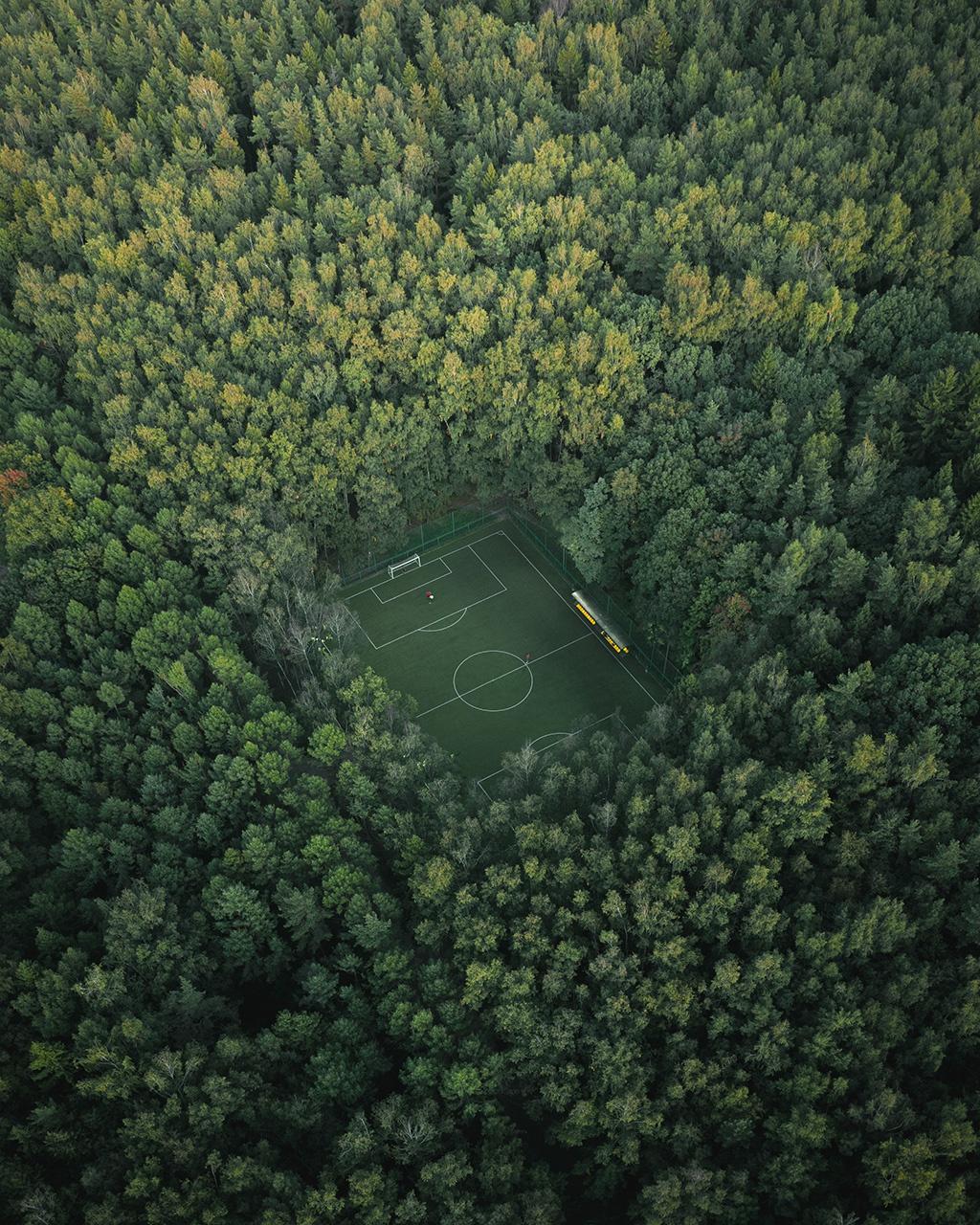 """Pikalov đã ghi lại khung cảnh sân bóng đá """"lọt thỏm"""" giữa công viên Meshchersky, Moscow, Nga. """"Với bức ảnh này, tôi đã cố gắng truyền đạt quy mô của một khu rừng xanh rậm rạp. Sân bóng ẩn khuất được bao quanh bởi những tán cây hùng vĩ là điểm nhấn."""" Màu xanh bao phủ của cây cối, sân bóng tạo ra ảnh chụp ấn tượng nhìn từ flycam."""